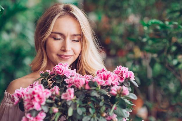 Ritratto di una giovane donna bionda che sente l'odore del fiore rosa