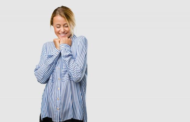Ritratto di una giovane donna bionda molto felice ed emozionato, alzando le braccia, celebrando una vittoria o successo, vincendo la lotteria
