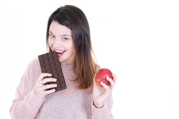 Ritratto di una giovane donna bruna morde il cioccolato con mela rossa in mano