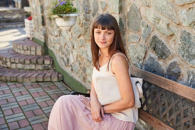 Ritratto di una giovane donna bruna seduta su una panchina