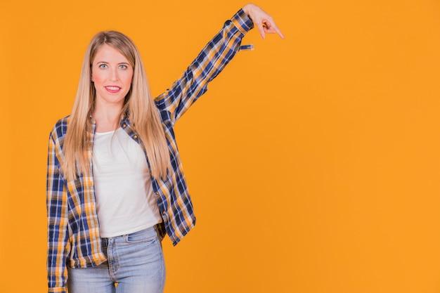 Ritratto di una giovane donna che alza le sue braccia contro uno sfondo arancione