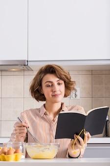 Ritratto di una giovane donna che batte le uova durante la lettura del ricettario