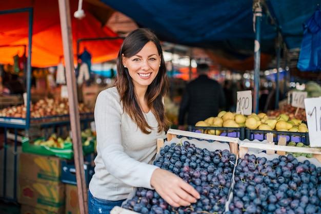 Ritratto di una giovane donna che compra l'uva al mercato di strada. guardando la fotocamera