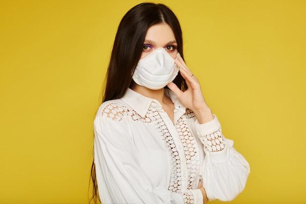 Ritratto di una giovane donna che indossa una maschera protettiva, guardando la telecamera, da vicino. epidemia di influenza, allergia alla polvere, concetto di inquinamento dell'aria. concetto di assistenza sanitaria