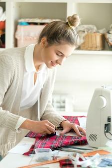 Ritratto di una giovane donna che lavora con un modello di cucito