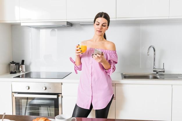 Ritratto di una giovane donna che manda un sms sul telefono cellulare che tiene vetro di succo a disposizione