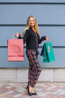 Ritratto di una giovane donna che mostra borse colorate in piedi contro il muro