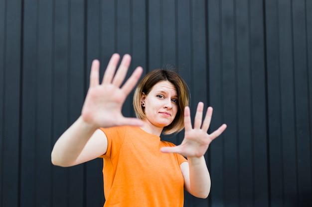 Ritratto di una giovane donna che mostra il gesto di arresto contro la parete nera