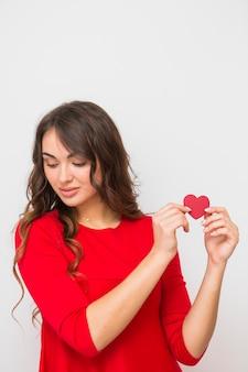 Ritratto di una giovane donna che mostra la carta di forma del cuore isolata su fondo bianco