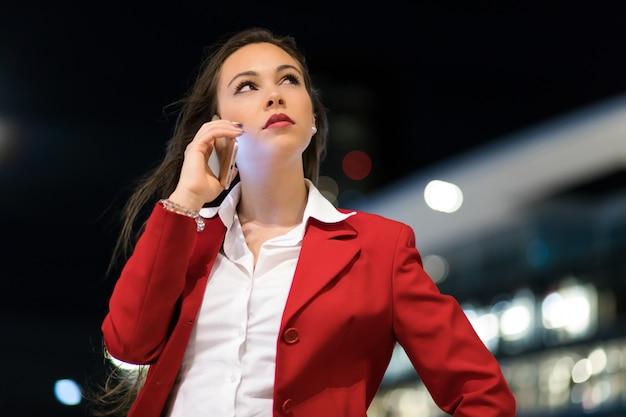Ritratto di una giovane donna che parla al telefono all'aperto in città a tarda sera