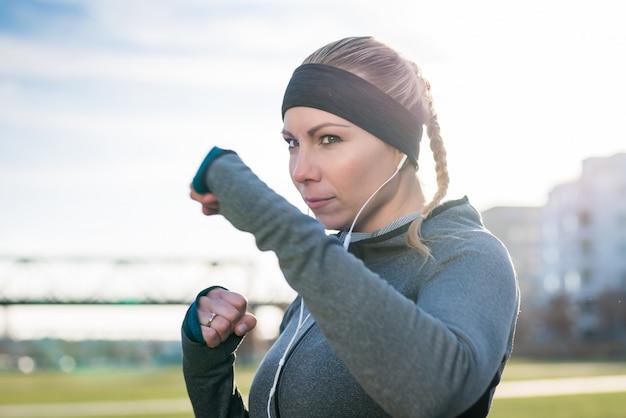 Ritratto di una giovane donna che pratica esercizio di boxe con confid
