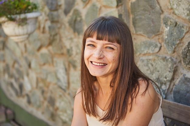 Ritratto di una giovane donna che ride con le lentiggini sul viso in estate su una strada cittadina