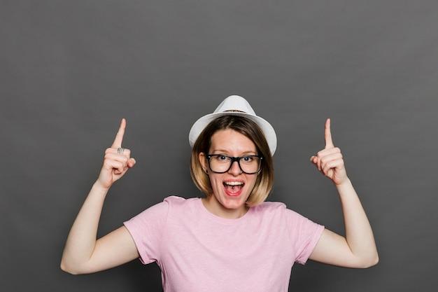 Ritratto di una giovane donna che ride indicando le dita verso l'alto contro la parete grigia