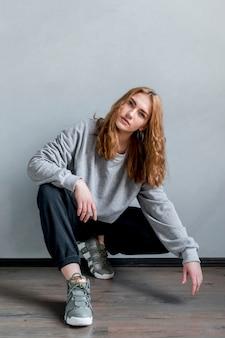 Ritratto di una giovane donna che si accovaccia sul pavimento di legno duro contro la parete grigia