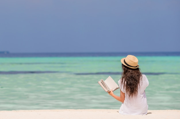 Ritratto di una giovane donna che si distende sulla spiaggia, leggendo un libro