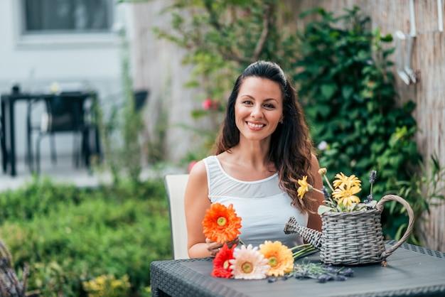 Ritratto di una giovane donna che si siede al tavolo di legno e aranging un bouquet di fiori.