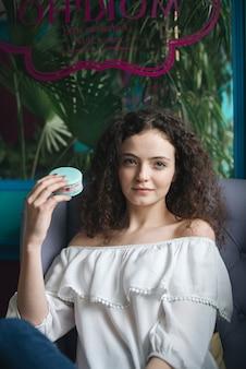 Ritratto di una giovane donna che si siede nel panino del gelato della tenuta del caffè