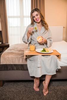 Ritratto di una giovane donna che si siede sul letto che mangia la fetta d'arancia e kiwi divisa in due