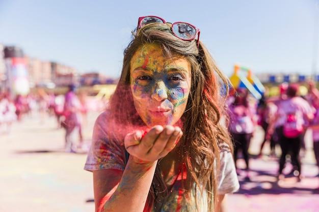 Ritratto di una giovane donna che soffia colore holi davanti alla telecamera