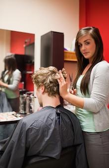 Ritratto di una giovane donna che taglia i capelli di un uomo