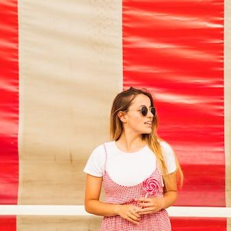 Ritratto di una giovane donna che tiene in mano il lecca-lecca rosso in cerca di distanza