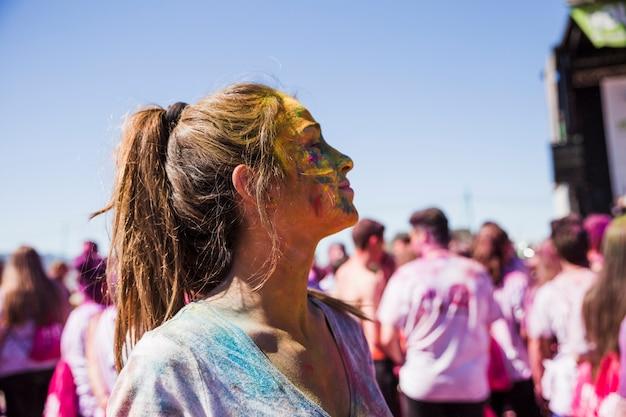 Ritratto di una giovane donna con il colore di holi sul viso