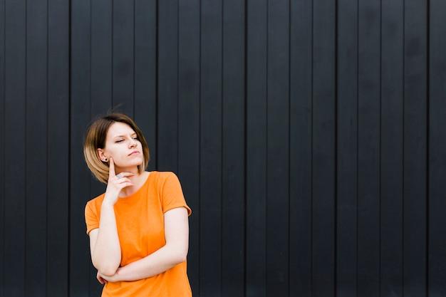 Ritratto di una giovane donna contemplata in piedi contro il muro nero