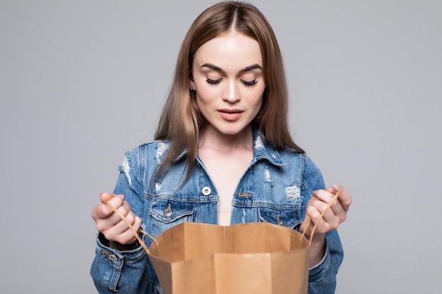 Ritratto di una giovane donna curiosa che guarda dentro i sacchetti della spesa sopra la parete grigia