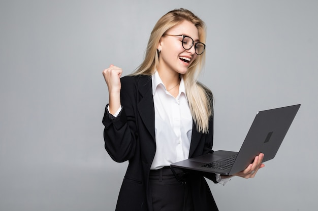 Ritratto di una giovane donna d'affari felice con un computer portatile con gesto di vittoria