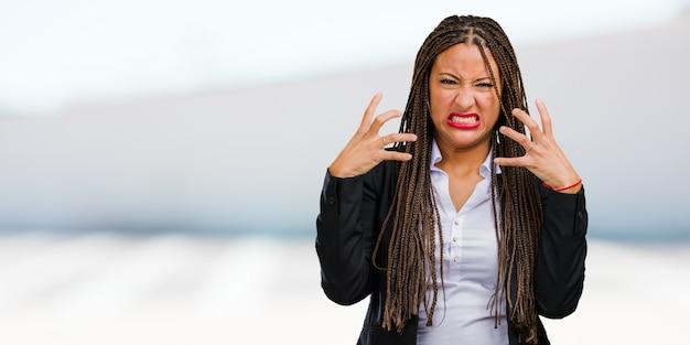 Ritratto di una giovane donna d'affari nero molto arrabbiato e sconvolto, molto teso, urlando furioso, negativo e pazzo