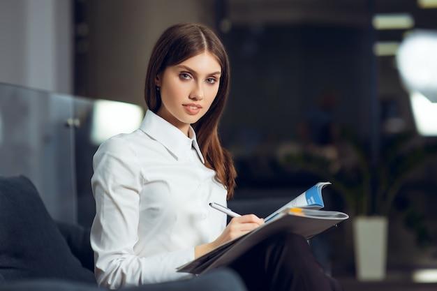 Ritratto di una giovane donna d'affari seduto nel suo posto di lavoro