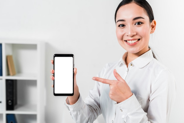 Ritratto di una giovane donna di affari asiatica felice che indica al telefono cellulare