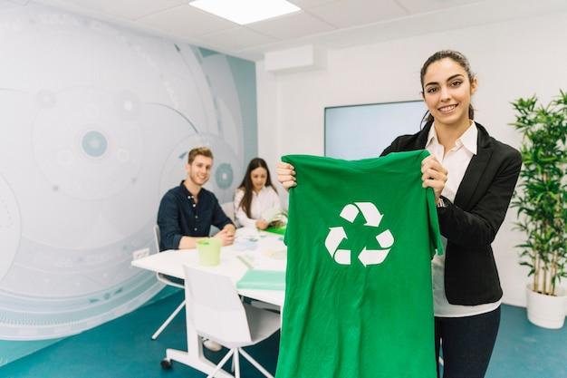 Ritratto di una giovane donna di affari felice che mostra maglietta verde con l'icona di riciclaggio