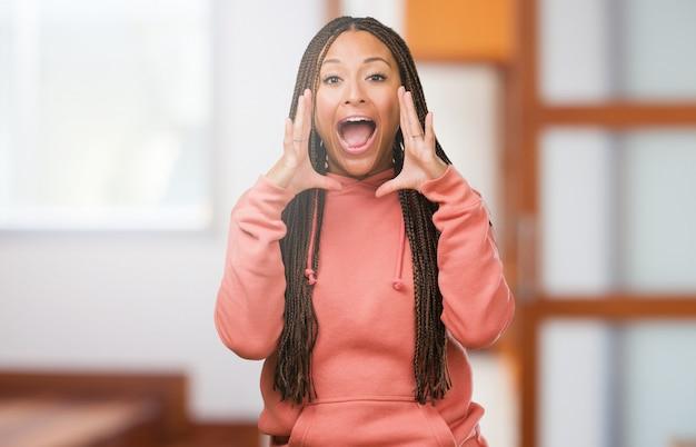 Ritratto di una giovane donna di colore che indossa le trecce che gridano arrabbiato