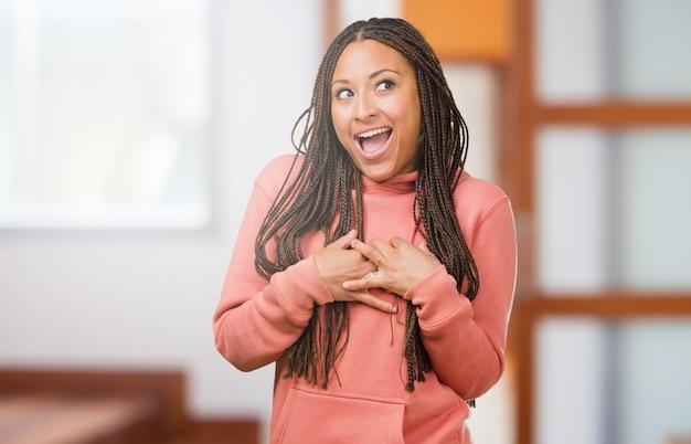 Ritratto di una giovane donna di colore che indossa le trecce facendo un gesto romantico