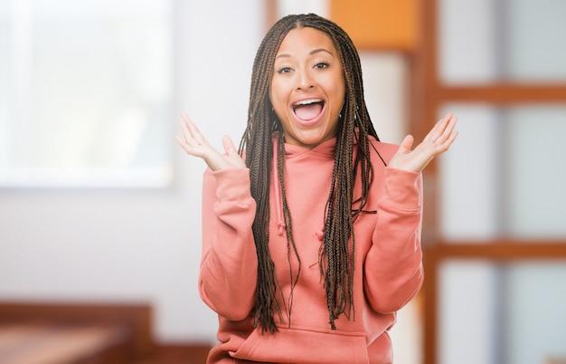 Ritratto di una giovane donna di colore che indossa le trecce sorpreso e scioccato