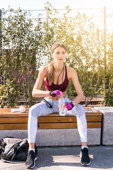 Ritratto di una giovane donna di forma fisica che si siede sul banco che apre la bottiglia di acqua