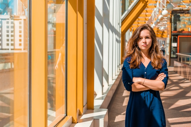 Ritratto di una giovane donna di successo in uno spazio moderno e luminoso sul ponte pedonale giallo