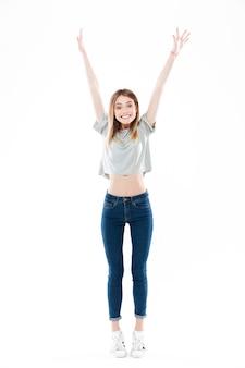 Ritratto di una giovane donna emozionante felice che sta e che celebra successo