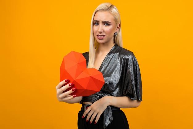 Ritratto di una giovane donna europea afflitta triste che tiene un cuore rosso nelle sue mani