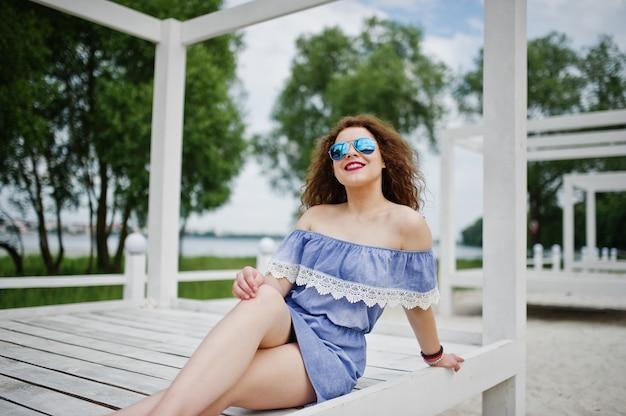 Ritratto di una giovane donna favolosa che indossa abito elegante in posa su una terrazza in legno bianca.