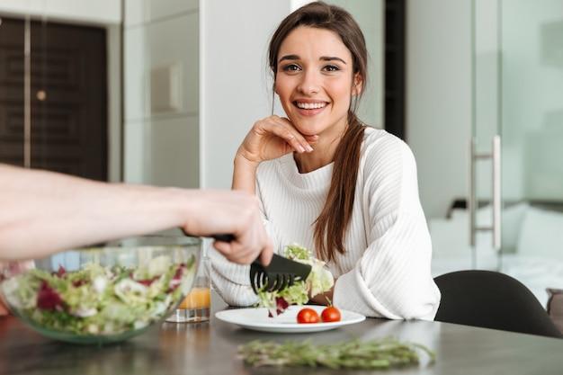 Ritratto di una giovane donna felice che mangia prima colazione sana