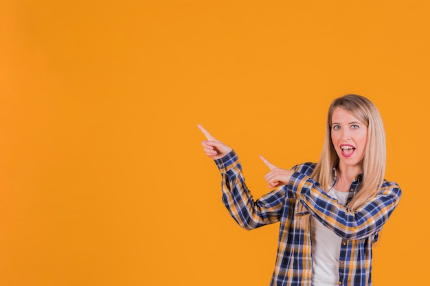 Ritratto di una giovane donna felice che punta le dita contro uno sfondo arancione
