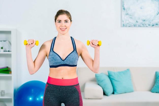 Ritratto di una giovane donna felice che si esercita con i dumbbells gialli a casa