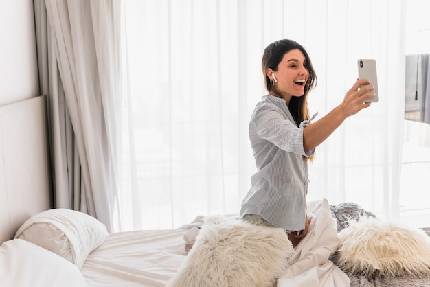 Ritratto di una giovane donna felice che si siede sul letto prendendo facendo videochiamata sul cellulare