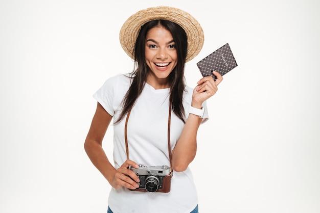 Ritratto di una giovane donna felice nella macchina fotografica della tenuta del cappello
