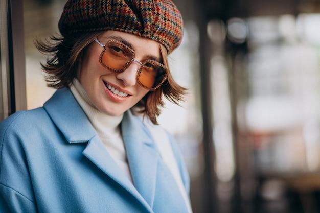 Ritratto di una giovane donna in occhiali da sole e cappello
