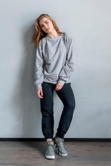 Ritratto di una giovane donna in piedi contro il muro grigio