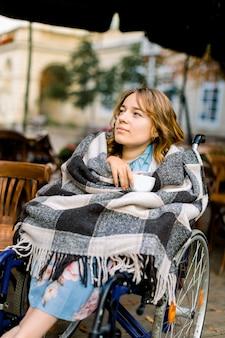 Ritratto di una giovane donna in sedia a rotelle che gode del suo giorno e che beve caffè in un caffè all'aperto.