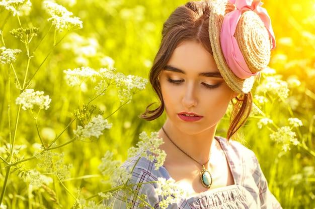 478a4a40ae44 Ritratto di una giovane donna in un cappello sull erba